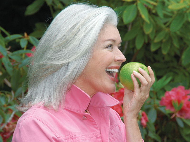 Lady eating and apple.